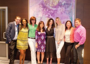Artist Mimi Saltzman (fourth from right) standing in front of one of her paintings at Bond New York's office with a group of Bond agents.