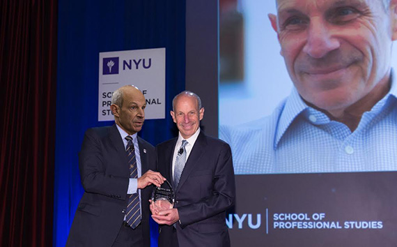 Jonathan Tisch presents Jonathan Tisch with the inaugural Jonathan Tisch award, while Jonathan Tisch happily looks on from the screen in the background