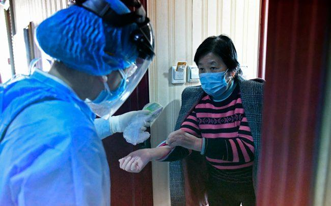 A medical staff member takes temperature for a woman at a hotel arranged as a quarantine center for people returning from overseas countrie (Photo by Wei Liang/China News Service via Getty Images)